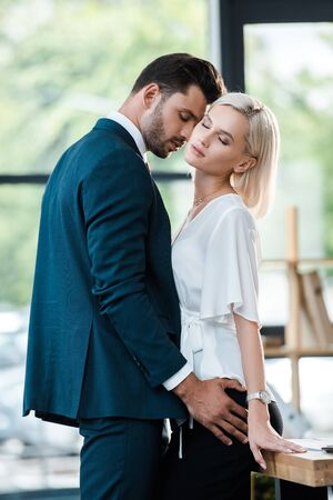 Photo pour handsome bearded man touching attractive woman with closed eyes - image libre de droit