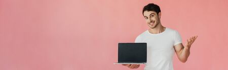 Foto de panoramic shot of smiling young man in white t-shirt showing laptop with blank screen isolated on pink - Imagen libre de derechos