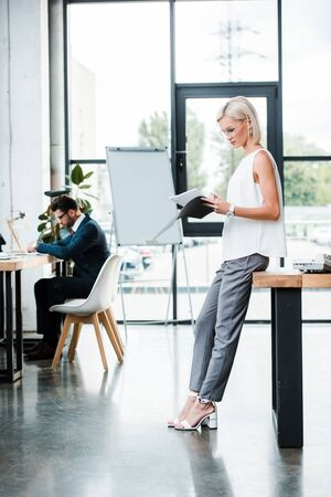 Photo pour selective focus of attractive businesswoman in glasses holding folder and documents near coworker in modern office - image libre de droit