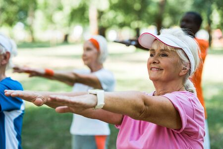 Photo pour selective focus of retired woman doing exercise near multicultural pensioners in park - image libre de droit