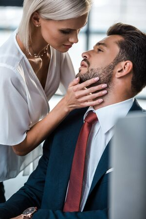 Photo pour selective focus of passionate blonde woman touching face of handsome man in office - image libre de droit