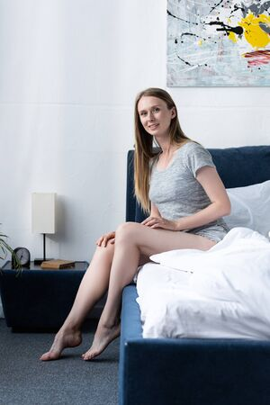Photo pour happy young woman in bed looking at camera in morning - image libre de droit