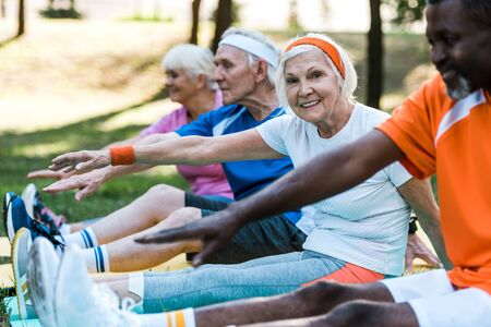 Photo for selective focus of multicultural retired women and men in sportswear exercising on fitness mats - Royalty Free Image