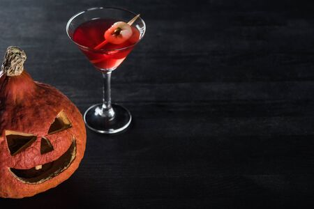 Photo for spooky Halloween pumpkin and red cocktail on black background - Royalty Free Image