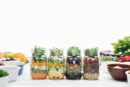 Photo for fresh vegetable salad in glass jars on wooden white table isolated on white - Royalty Free Image