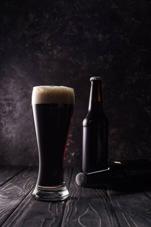 Foto per bottles and glass of beer in shadow on wooden table - Immagine Royalty Free