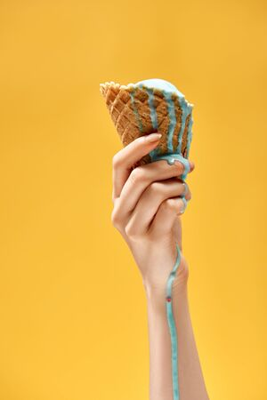 Foto de cropped view of woman holding delicious melted blue ice cream in crispy waffle cone isolated on yellow - Imagen libre de derechos