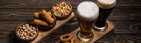 Foto per panoramic shot of glasses of dark and light beer near bowls with peanuts, pistachios, fried cheese and onion rings on wooden table - Immagine Royalty Free