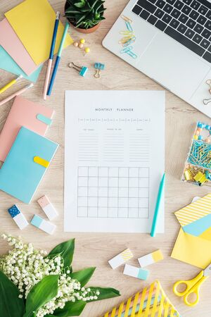 Photo pour top view of monthly planner, stationery, flowers and laptop on wooden table - image libre de droit