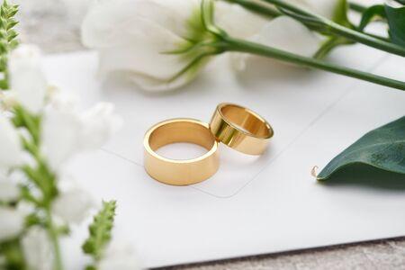 Photo pour selective focus of wedding rings on white envelope near white eustoma flowers - image libre de droit