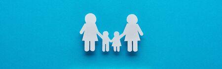 Photo pour top view of paper cut lesbian family holding hands on blue background, panoramic shot - image libre de droit
