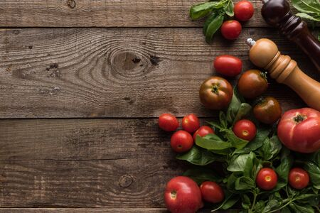 Foto für top view of tomatoes, spinach, pepper mill and salt mill on wooden table - Lizenzfreies Bild