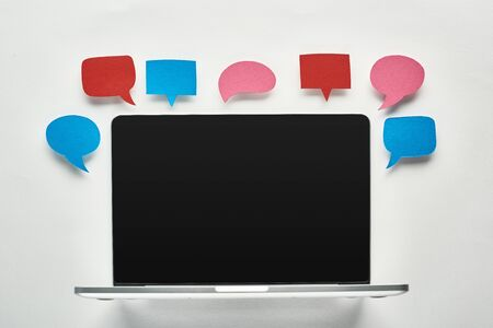 Photo pour laptop with blank screen on white background near empty colorful speech bubbles, cyberbullying concept - image libre de droit