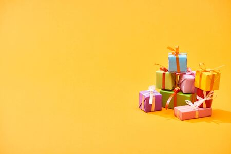 Photo for stack of colorful festive boxes on bright orange background - Royalty Free Image