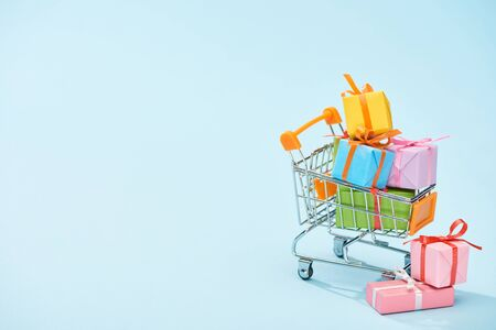 Foto de festive wrapped presents in shopping cart on blue background with copy space - Imagen libre de derechos