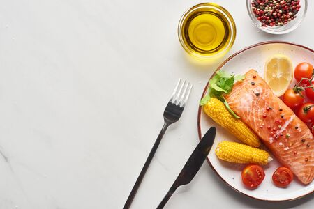 Photo for top view of raw salmon steak with corn and tomatoes on plate near cutlery, oil and peppercorns on marble table - Royalty Free Image