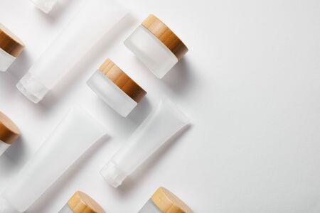 Foto de flat lay of cream tubes and jars with wooden caps on white - Imagen libre de derechos