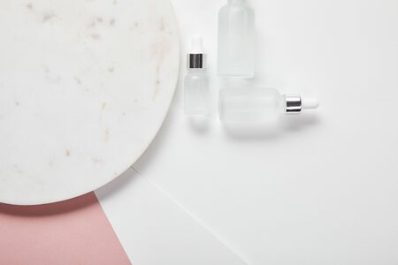 Photo for top view of cosmetic glass bottles near plate on white pink surface - Royalty Free Image