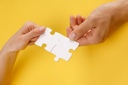 Photo pour cropped view of man and woman matching pieces of white puzzle on yellow background - image libre de droit