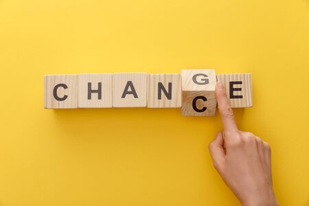 Photo pour cropped view of woman switching wooden cube from word change to chance on yellow background - image libre de droit