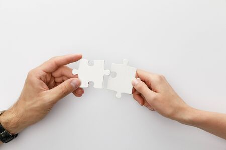 Photo pour cropped view of woman and man holding pieces of jigsaw puzzle on white background - image libre de droit