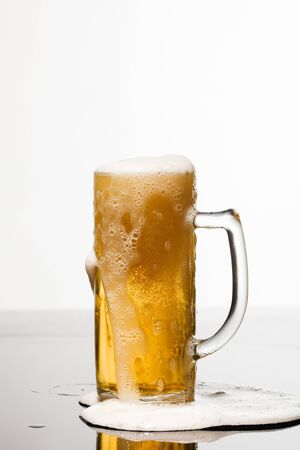Photo pour wet glass of beer with foam and puddle on surface isolated on white - image libre de droit