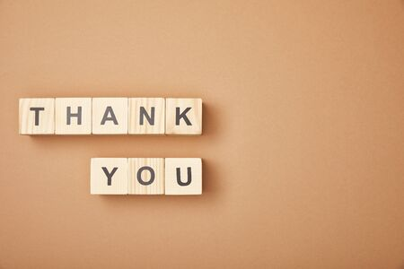 top view of wooden cubes with thank you lettering on beige background with copy space