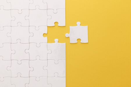 Photo for top view of white jigsaw puzzle on yellow background - Royalty Free Image