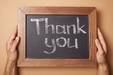 cropped view of man holding chalkboard with thank you lettering