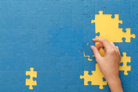 Photo pour cropped view of woman matching blue jigsaw puzzle on yellow background - image libre de droit