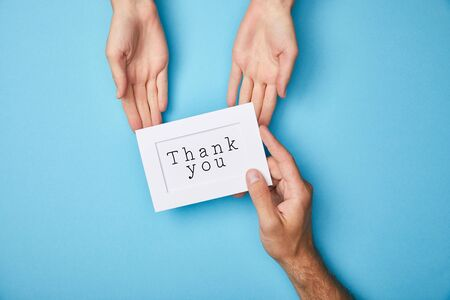 Foto de cropped view of man giving white card in frame with thank you lettering to woman on blue background - Imagen libre de derechos
