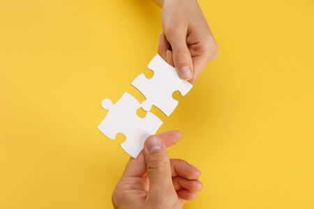 Photo pour cropped view of woman and man matching pieces of white puzzle on yellow background - image libre de droit