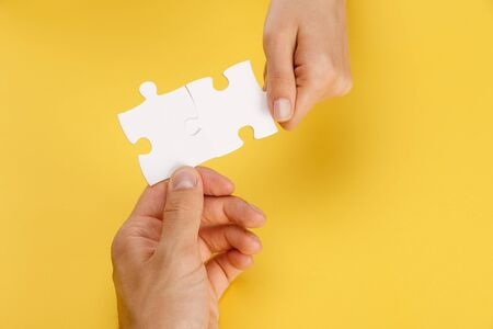Photo pour cropped view of man and woman holding pieces of white puzzle on yellow background - image libre de droit