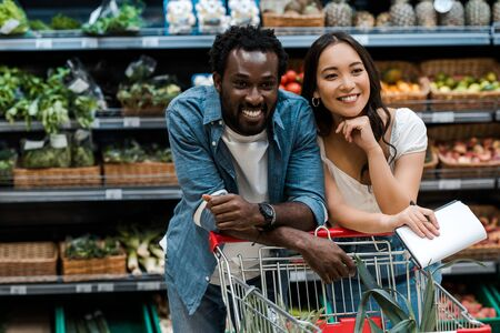 Photo for cheerful interracial couple smiling in supermarket near shopping cart - Royalty Free Image