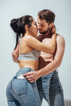 Foto de sexy couple hugging and trying to kiss while man putting off condom from jeans of girl - Imagen libre de derechos