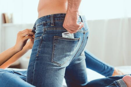 Photo pour cropped view of young man in blue jeans getting condom from pocket near girlfriend - image libre de droit