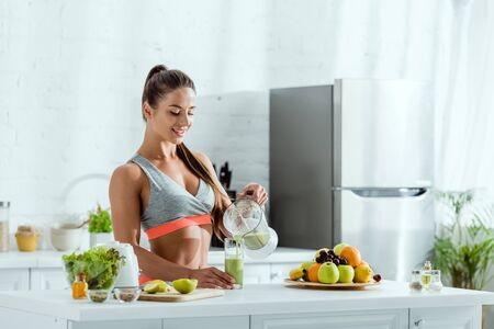 Photo pour happy woman with sportswear pouring smoothie in glass near fruits - image libre de droit