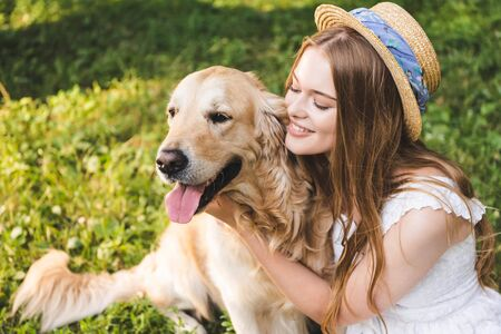 Photo for beautiful girl in white dress and straw hat hugging golden retriever while sitting on meadow and looking at dog - Royalty Free Image