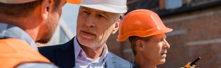 Photo for panoramic shot of constructor near businessman and coworker - Royalty Free Image