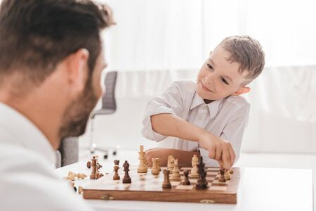 Foto de selective focus of dad and son playing chess together at home - Imagen libre de derechos
