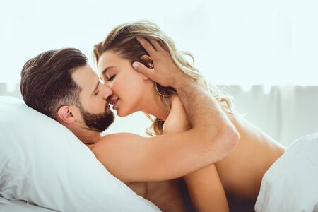 Photo pour handsome young man kissing beautiful girlfriend while lying in bed - image libre de droit