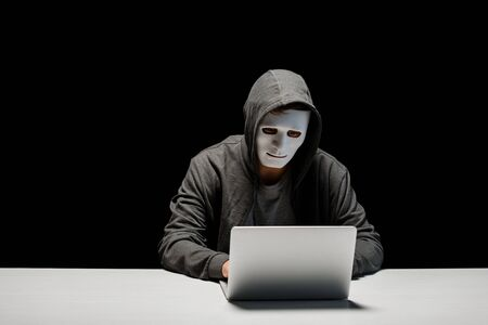 Photo pour anonymous internet troll in mask typing on laptop keyboard isolated on black - image libre de droit