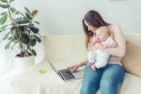 Photo pour attractive mother holding her child and using laptop in apartment - image libre de droit