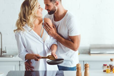 Photo pour handsome young man hugging cheerful girlfriend preparing breakfast on frying pan - image libre de droit
