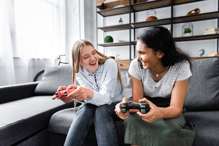 KYIV, UKRAINE - JULY 10, 2019: multicultural friends sitting on sofa and playing video game in apartment