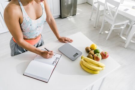 Foto de cropped view of woman holding pen near notebook with lettering and fruits - Imagen libre de derechos