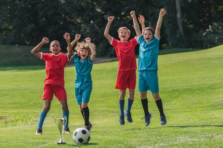 Photo pour happy multicultural gesturing near trophy and football - image libre de droit