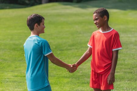 Photo pour happy multicultural kids shaking hands outside - image libre de droit