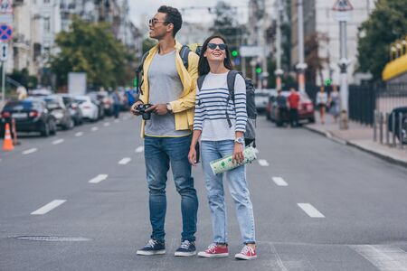 Photo pour Woman holding map and standing on road near bi-racial friend with backpack and digital camera - image libre de droit