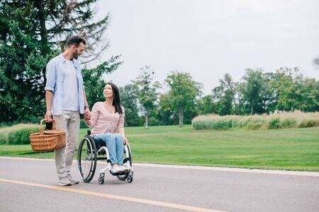 Photo pour handsome man with straw basket holding hands with disabled girlfriend while walking in park together - image libre de droit